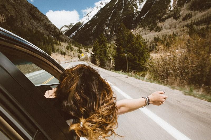 femme dans une voiture qui passe la tête par la fenêtre