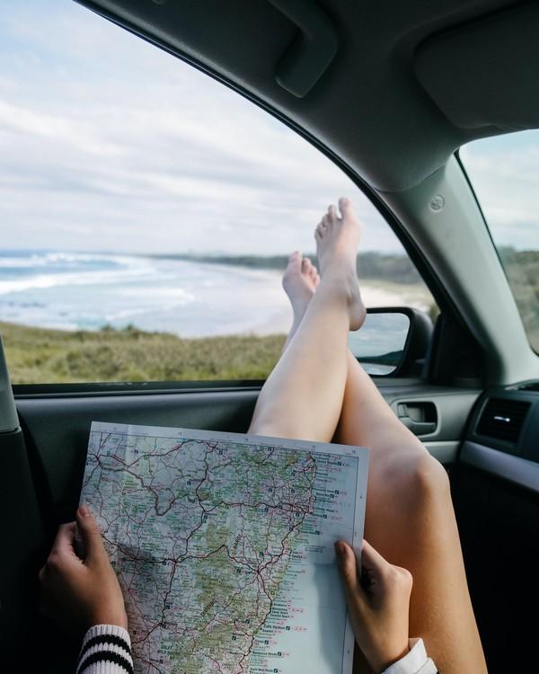 femme qui tient une carte routière dans une voiture