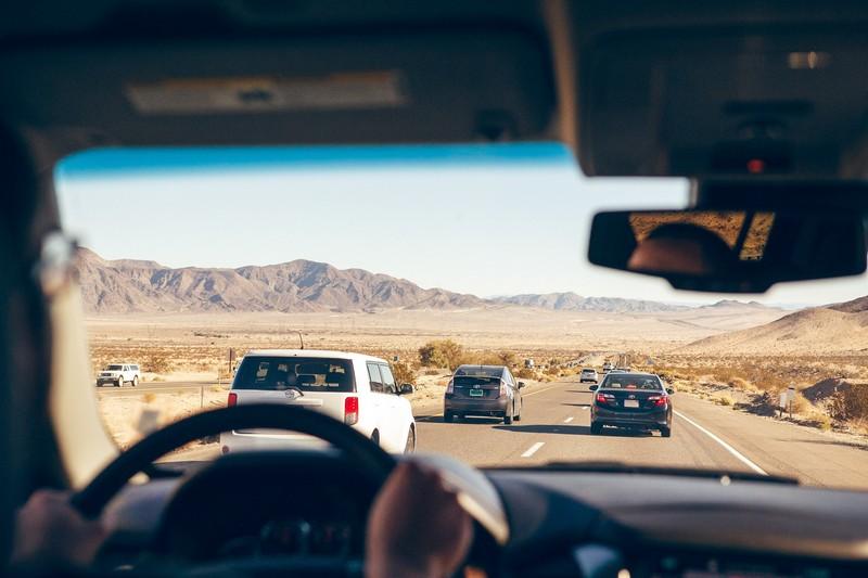 homme qui conduit sur une route avec d'autres voitures devant lui